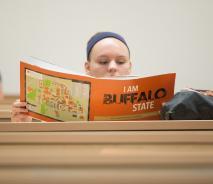 Student reading a Buffalo State viewbook